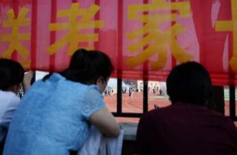 """影像力丨考场外的温情:家长在考场外围栏边目送考生入场 用手机记录""""历史瞬间"""""""