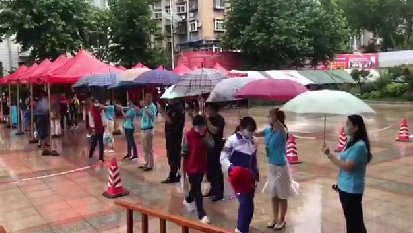 26秒丨中考碰上下雨天 老师们用雨伞撑起爱的考生通道