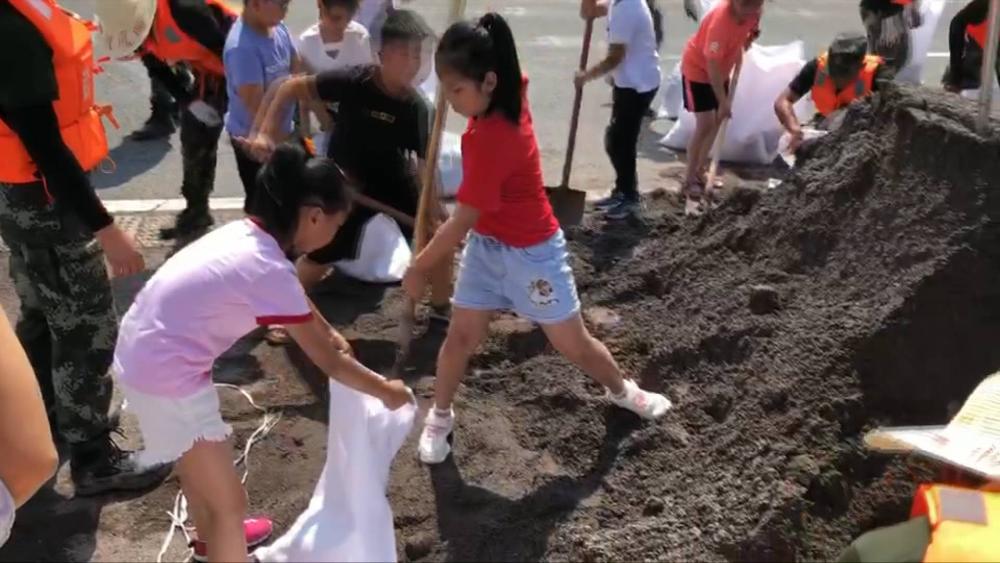 装沙袋加固堤坝 在安徽防汛的武警大哥哥们有了小帮手