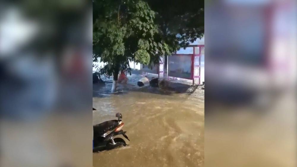 43秒丨肥城一女子暴雨中摔倒被冲走 三名路人扑入水中将其救起