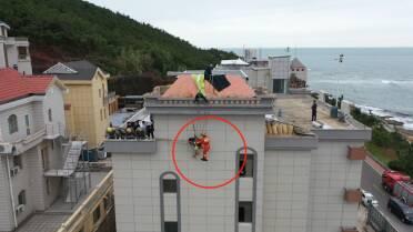 42秒|因大风滑翔伞失控,威海一男子被挂在酒店外墙上