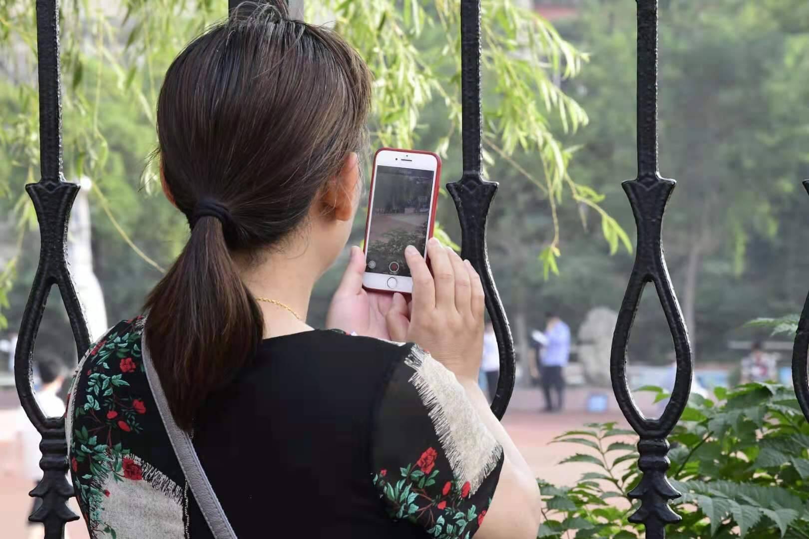 直击山东高考丨送考家长全程暖心陪伴,用手机记录孩子人生重要时刻