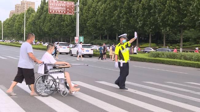 """潍坊:考生坐轮椅参加高考 考点""""守护者""""接力护送"""