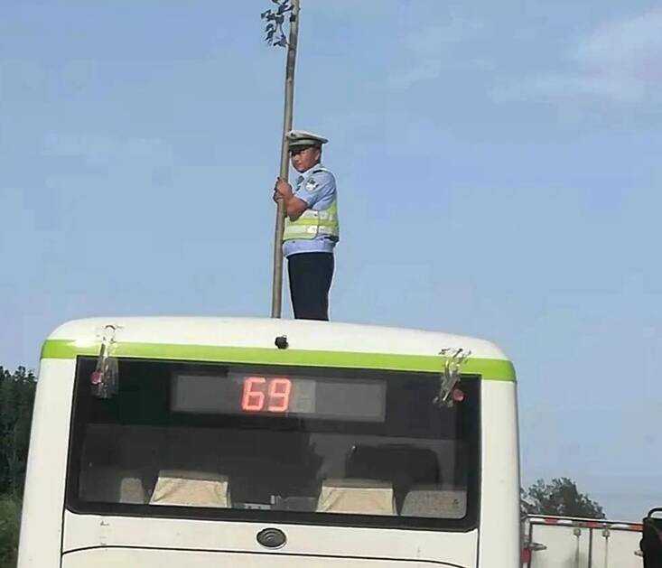 """最美瞬间!大风刮落国防光缆 聊城这位交警爬上车顶把自己站成了一面""""旗"""""""