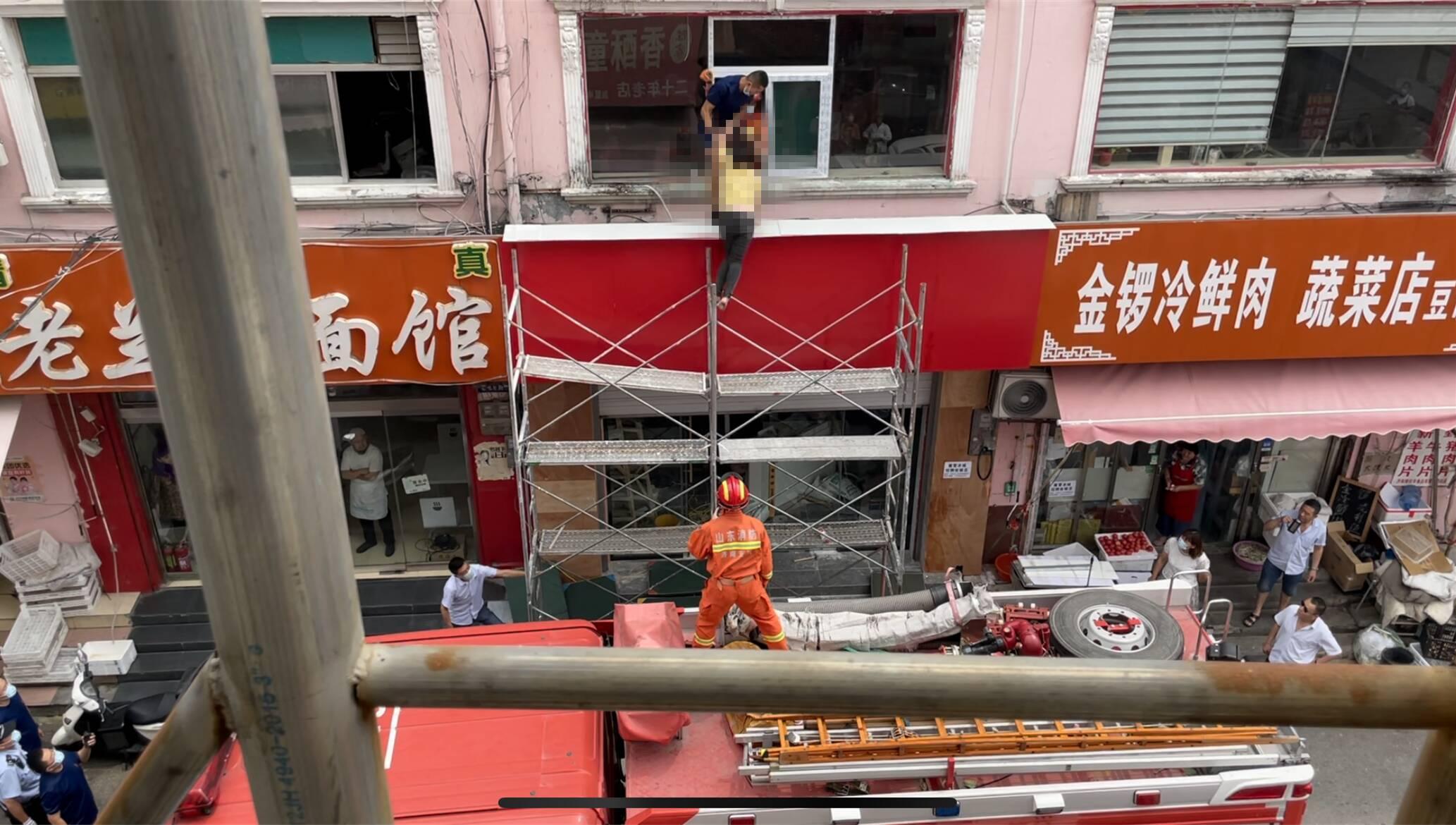 济南一女子因家庭纠纷爬上五米高脚手架 消防员飞身救下